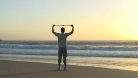 Man som gör övningar på en strand stock video