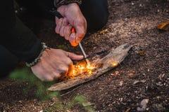Man som gör brand med fnöskepolyporesvampen i en skog royaltyfri bild