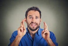 Man som gör en önska som korsar hans fingrar arkivfoton