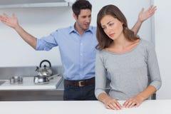 Man som gör en gest till frun under en tvist arkivfoto