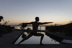 Man som gör krigaren silhouetted av pölen Royaltyfri Fotografi