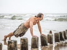 Man som gör liggande armhävningar på stranden Royaltyfria Bilder