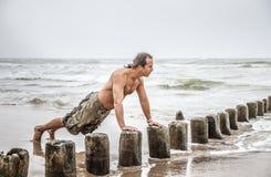 Man som gör liggande armhävningar på stranden Arkivbild