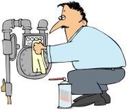 Man som gör ren en gasmeter Arkivfoto