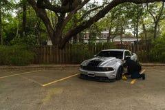 Man som gör ren en silver Ford Mustang royaltyfri foto