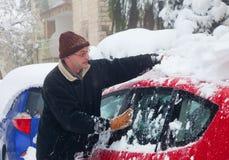Man som gör ren hans bil från snö Arkivbilder