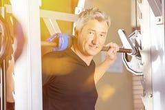 Man som gör tyngdlyftning i idrottshall Royaltyfria Bilder
