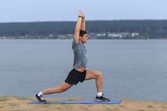 Man som gör utomhus- yoga För yogakondition för ung man som praktiserande övning är utomhus- på det härliga havet Fotografering för Bildbyråer