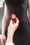 Man som ger cirkeln i ask till flickvännen och frågar henne att att gifta sig Arkivbilder