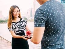 Man som ger en gåvaask till hans kvinnliga partner Lyckligt förhållande i utomhus- plats Förälskelse- och förhållandebegrepp Royaltyfria Bilder