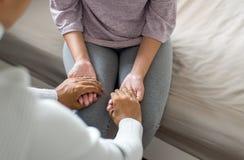 Man som ger handen till den deprimerade kvinnapatienten, personlig utveckling inklusive perioder för livcoachningterapi och anför royaltyfri foto