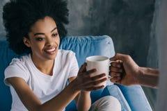 Man som ger koppen kaffe till afrikanen arkivfoton