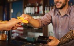 Man som ger kreditkorten till bartendern i bar royaltyfri foto