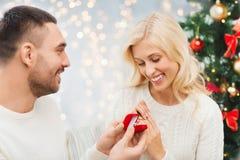 Man som ger kvinnaförlovningsringen för jul royaltyfria foton