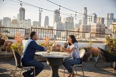 Man som ger kvinnagåvan, som de firar på takterrass med stadshorisont i bakgrund royaltyfri fotografi
