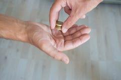 Man som ger mynt till en annan person Fotografering för Bildbyråer