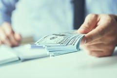 Man som ger pengar oss dollarsedlar och rymmer kassa i händer Pengarkrediteringsbegrepp Tonad bild royaltyfri foto