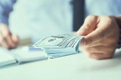 Man som ger pengar oss dollarsedlar och rymmer kassa i h?nder Pengarkrediteringsbegrepp Tonad bild arkivbilder