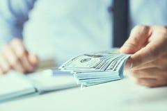 Man som ger pengar oss dollarsedlar och rymmer kassa i h?nder Pengarkrediteringsbegrepp Tonad bild fotografering för bildbyråer