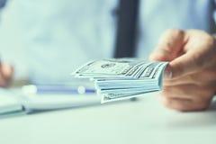 Man som ger pengar oss dollarsedlar och rymmer kassa i h?nder Pengarkrediteringsbegrepp Tonad bild arkivfoton