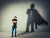 Man som gjuter en superhero med uddeskugga på väggen stock illustrationer