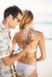 Man som gör ett solsymbol på kvinnas baksida, medan applicera en sunscreenlotion Arkivbilder