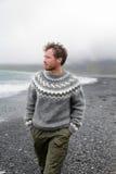 Man som går på den svarta sandstranden på Island Royaltyfri Bild