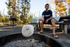 Man som grillar en marshmallow över brandgrop på en campingplats royaltyfri bild