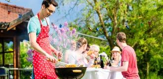 Man som grillar kött på det trädgårds- grillfestpartiet Fotografering för Bildbyråer