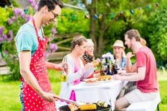 Man som grillar kött på det trädgårds- grillfestpartiet Royaltyfri Bild
