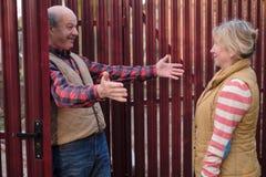 Man som hälsar hans vän nära det röda staketet som önskar att krama henne royaltyfria foton