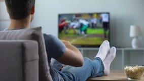 Man som håller ögonen på amerikansk fotboll äta mellanmål på soffahemmet, helgfritid stock video