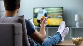 Man som håller ögonen på amerikansk fotboll äta mellanmål på soffahemmet, helgfritid royaltyfri fotografi
