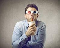Man som håller ögonen på en film 3D Fotografering för Bildbyråer