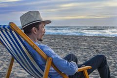 Man som håller ögonen på solnedgången på stranden Royaltyfri Fotografi