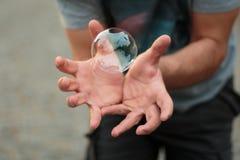 Man som håller en såpbubbla i hans öppna händer royaltyfri bild