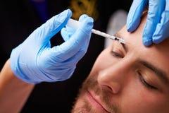 Man som har Botox behandling på skönhetkliniken Fotografering för Bildbyråer