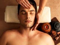 Man som har den head massagen i brunnsortsalongen Arkivfoto