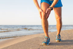 Man som har en smärta i hans knä royaltyfri fotografi