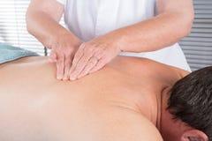 Man som har en tillbaka massage i brunnsortwellness royaltyfri foto