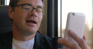 Man som har en video pratstund på mobil under drevet arkivfilmer