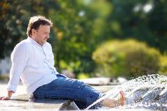 Man som har gyckel i en stadsspringbrunn Royaltyfri Bild