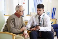 Man som har kemoterapi med doktor Using Digital Tablet Royaltyfri Bild