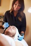 Man som har kosmetisk behandling för Dermo slitning på Spa Arkivbild