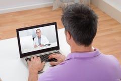 Man som har video pratstund med doktorn arkivfoton