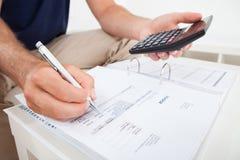 Man som hem beräknar finanser Arkivfoton