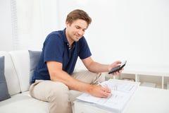 Man som hem beräknar finanser på tabellen Fotografering för Bildbyråer