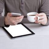 Man som hemifrån arbetar genom att använda den smarta telefon- och anteckningsbokdatoren, händer för man` s genom att använda den Fotografering för Bildbyråer
