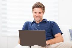 Man som hemma använder bärbara datorn på soffan Royaltyfria Bilder