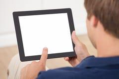 Man som hemma använder den Digital minnestavlan Royaltyfri Fotografi